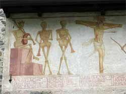Chiesa di San Vigilio - Pinzolo - Danza macabra - raffigura la Morte che suona la cornamusa accompagnata da due scheletri con la tromba. Segue Cristo in croce che pure la subì.Sotto le figure un testo scritto in lingua locale fornisce l'ironico e sarcastico commento alle figure.