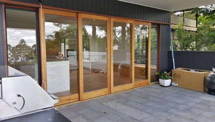 Centre opening timber sliding doors, stacking externally over wall, with glass louvre sidelights for ventilation when doors are closed. Opening out from kitchen to outdoor entertaining area // via Allkind