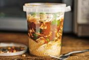 Plastic container or North African chicken soup with shredded chicken, ras el hanout, couscous, and preserved lemon