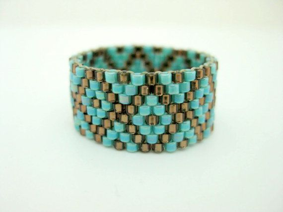 A stylish peyote ring! Made of Japanese delica beads in silver lined brown and turquoise. It is very comfortable to wear and ligthweight. This ring is 3/8(1,1cm) wide and size 8 (56-57). Check out my other beaded rings in many different colors, styles and designs: http://www.etsy.com/shop/MadeByKatarina?section_id=5864177 For other sizes and colors please feel free to contact me. Thank you for looking and have a nice day