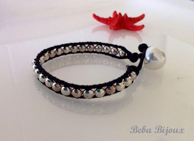 Bracciale con filo nero e pietre in metallo color argento. Chiusura con asola e perla.