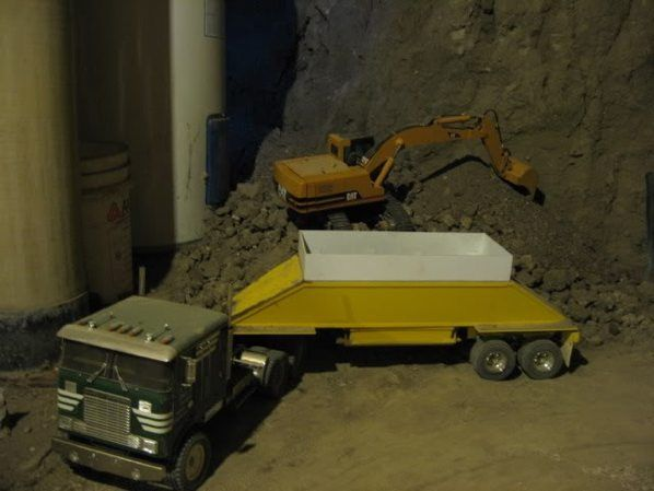 Man digs out basement with R/C construction equipment models