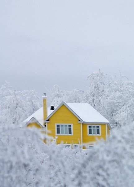 yellow painted house amidst winter