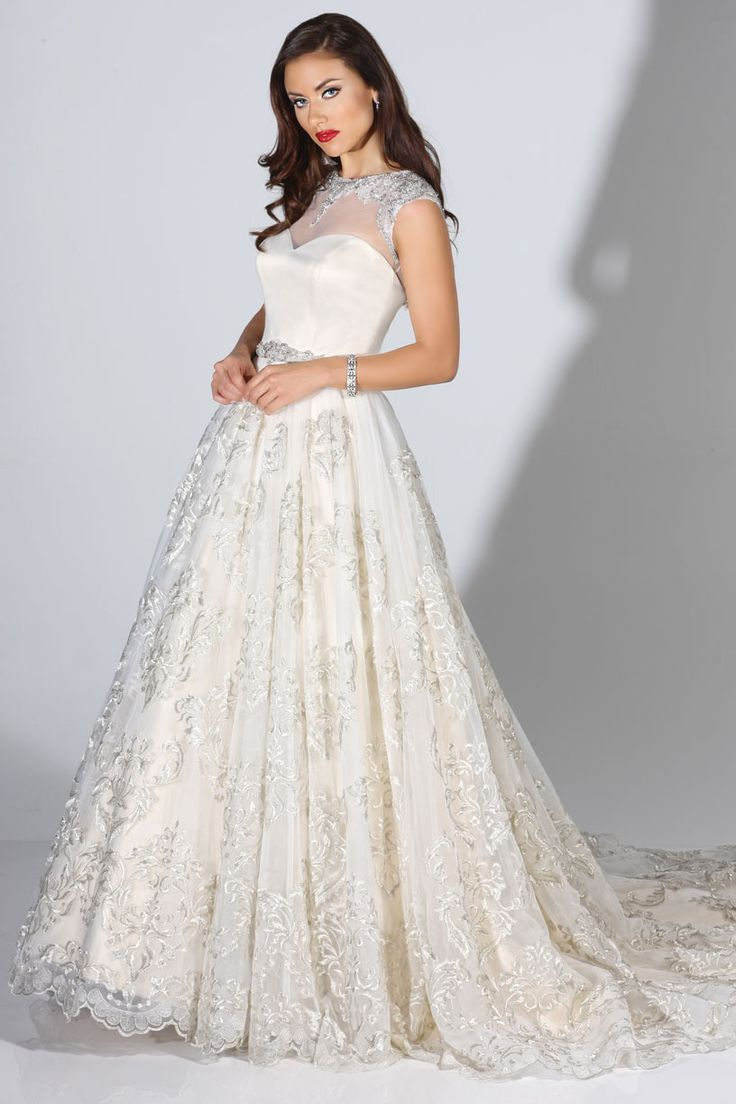 This Cristiano Lucci offers a textured ballgown skirt and beautiful illusion neckline! Perfect wedding dress with classic styling.
