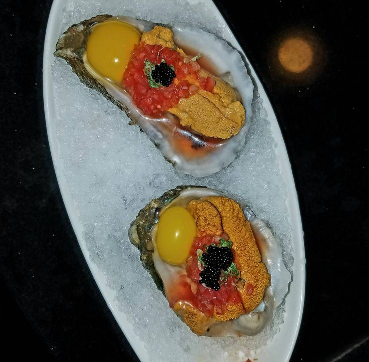 Raw oyster with uni and a quail egg. Des Moines Iowa.