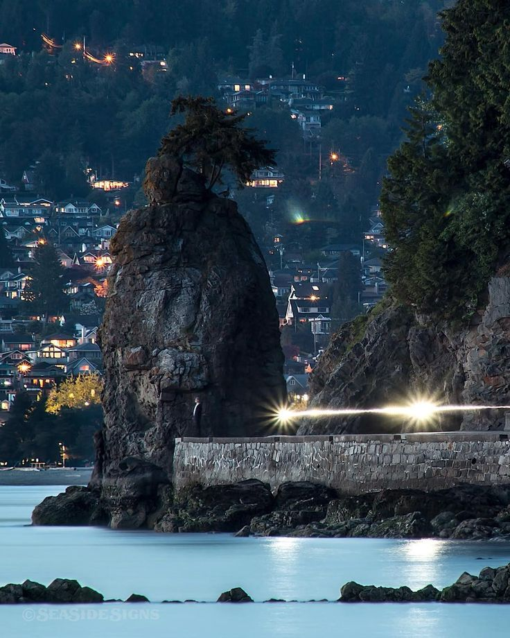 Streaking Siwash Rock Blue hour along the Seawall in Stanley Park. A bicyclist passes Siwash Rock with headlights on. In the distance you can see Ambleside Beach and houses in West Vancouver. Shot from Third Beach in Stanley Park Vancouver British Columbia Canada May 1 2016 Click the LINK in my bio to see the Full Length Photo on my Facebook Page #SiwashRock #StanleyPark #Seawall #Nature_Brilliance