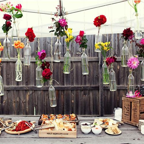 A bevy of clear bottles filled with sprigs of blooms and hung with twine.