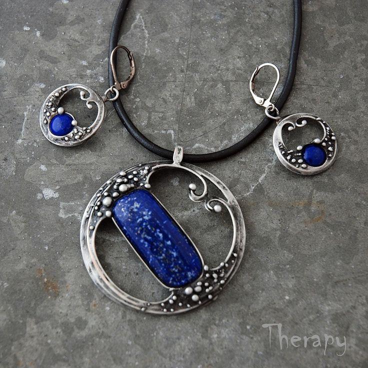 Souprava+s+lapisem+lazuli+Cínem+pájená+souprava+přívěsku+a+náušnic+s+kvalitním+tmavě+modrým+lapisem+lazuli.+Velikost+přívěsku+je+5,2+x+4,7+cm,+zavěšeno+na+černé+kulaté+kůži+o+délce+45+cm.+Velikost+náušnic+bez+háčku+je+2,5+x+2+cm,+délka+s+háčkem+4+cm.+Zavěšeno+na+uzavřených+háčcích+z+běžného+bižuterního+kovu.V+případě+potřeby+je+lze+vyměnit+za+háčky...
