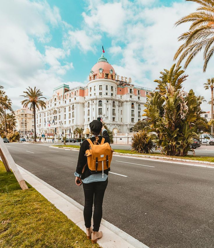 A girl taking a photograph for Instagram of the famous hotel in Nice, France. #thisisnice #springvacations #visitnice
