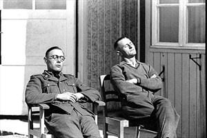 """Zwei SS-Leute machen Pause von der Arbeit im Konzentrationslager Mauthausen (Datum unbekannt). Ein irritierendes Zeugnis des KZ-""""Alltags""""."""