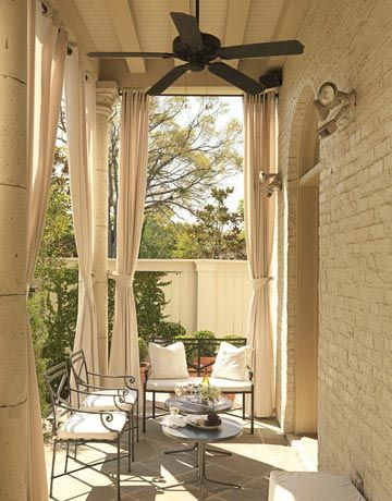 One of four outdoor seating areas, draperies and a ceiling fan provide a cool respite from the sun.