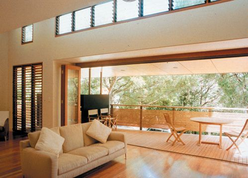 A contemporary living room has a wide bifold-door opening to a covered verandah providing fresh air and shade.