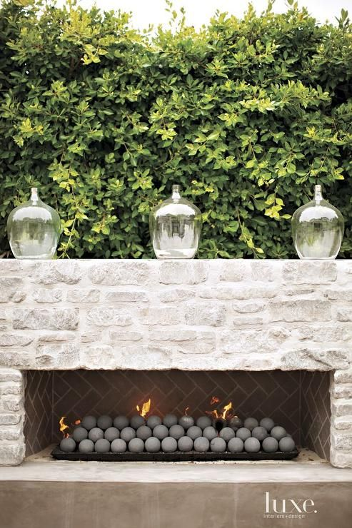 Chic patio features a pair of wicker sofas facing each other across from a weathered teak coffee table alongside weathered teak end tables placed in front of a white stone fireplace accented with a taupe herringbone firebox topped with hand blown jars.