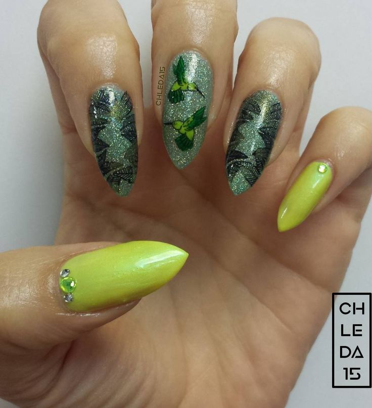 Thumb & pinky with neon yellow for base with rhinestones added near cuticles. Pointer, middle & ring with green holo for base. Pointer & ring with stamped palm leaves in olive green & sparkle black. Middle with reverse stamp design of neon yellow & green