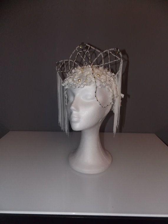 Tocado inspirado en el Cisne Blanco.  Realizado sobre una diadema y utilizando raso, brillantes, flecos, pedrería y perlas para adornarlo.  Creado