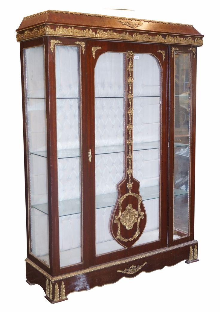 Een mahoniefineer 1-deurs vitrinekast met eclectisch goudkleurig beslag van o.a. paarden, guirlandes, strikjes en figuren, glazen planken en gecapitonneerde witstoffen achterwand