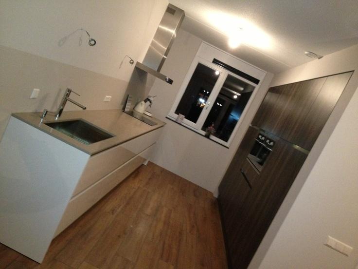 Witte greeploze keuken met een houtkleurige kastenwand in bouwkundige nis. De wand achter het kook-en spoelmeubel is deels gecaot dus ideaal schoon te maken — in Gorinchem, Zuid-Holland.