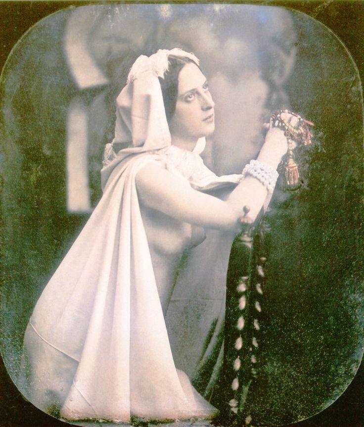 Mujer reza arrodillada junto a una silla. Lleva un vestido de novia blanco, abierto por la parte de delante, que deja ver su pecho.  Daguerrotipo estereoscópico coloreado a mano. 1850.