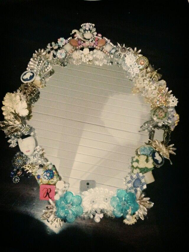 Spiegel mit Rahmen aus Broschen.