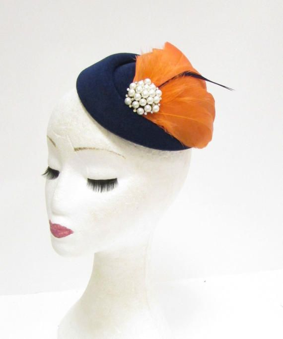 Beautiful vintage style feather pillbox fascinator This item is stunning and perfect for adding vintage style glamour to your hair. Featuring coral-orange and navy blue feathers, ivory white faux pearl and silver rhinestone centrepiece and navy felt feel pillbox fascinator. This