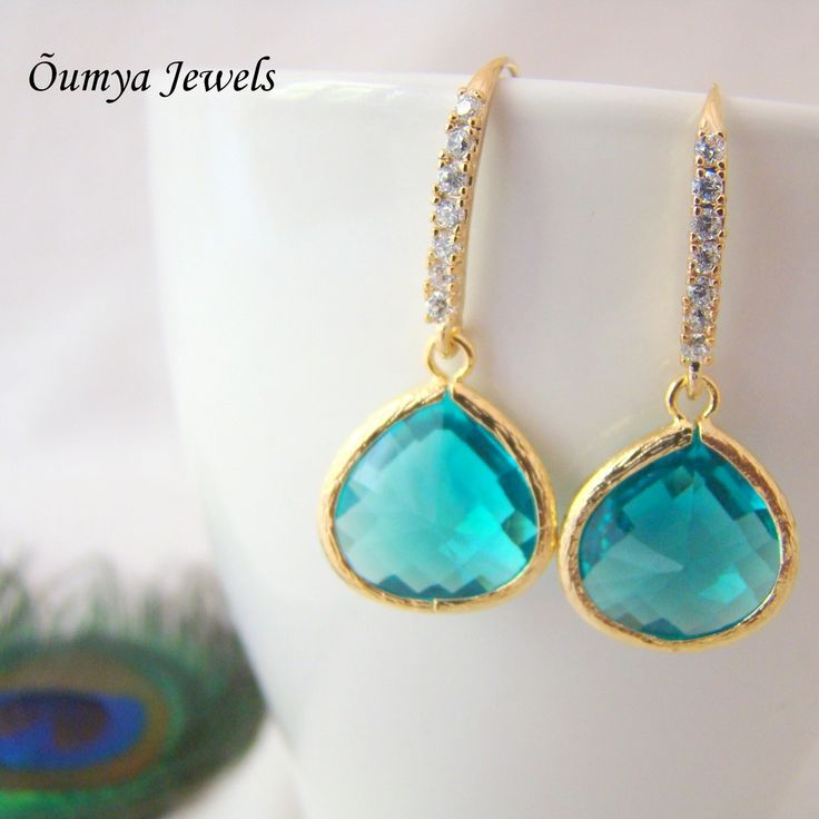 Cubiz zirconia (kind of diamonds) stud, gold plated earrings with a huge Blue coloured glass drop. These beautiful piece of earrings are available at theamalaanstore.com