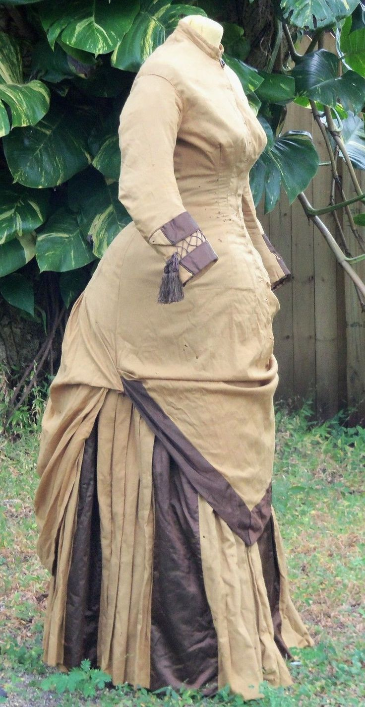 lady's Traveling or Day Dress from about 1880. Consisting of a polonaise bodice and underskirt skirt, it is made of light, soft tan wool (cashmere, I think) trimmed with rich dark brown silk satin. The polonaise bodice is lined with dark brown cotton. Its skirt portion is unlined. The bodice fastens with 14 buttons (missing). It's cuffs are satin with faux lacing and silk tassels.