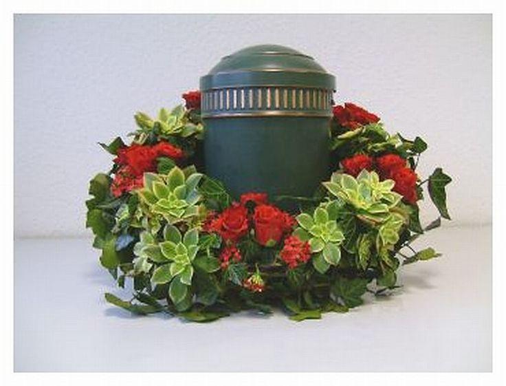 Die Urne wird im Trauerkranz abgestellt. Als Unterlage dienst ein speziller Urnen- Steckschaum-Ring mit Boden.Das Blumen-Gesteck wurde speziell für das Urnenbegräbnis angefertigt