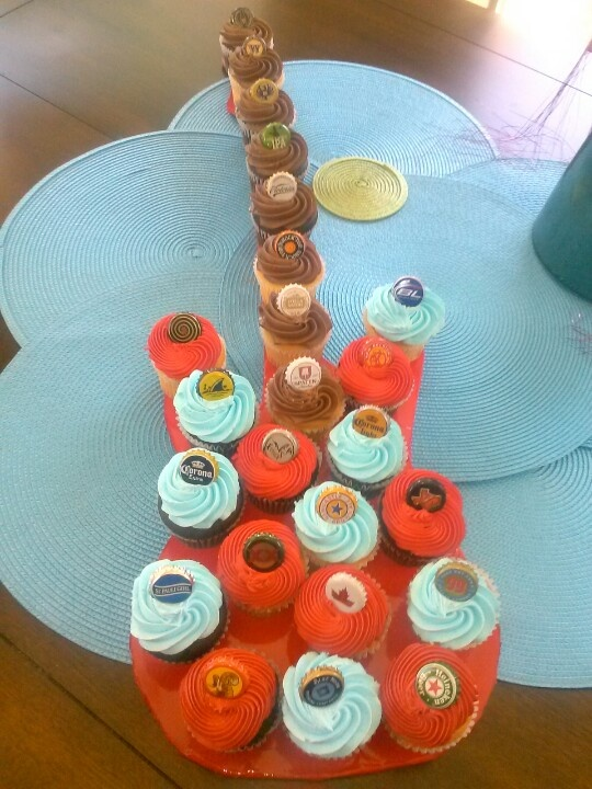 Guitar Cupcake! I cut out a guitar shape out of cardboard, and spray painted it red. Placed different beer caps on the cupcakes as decor. It held 24 cup cakes. Great for a guys bday!