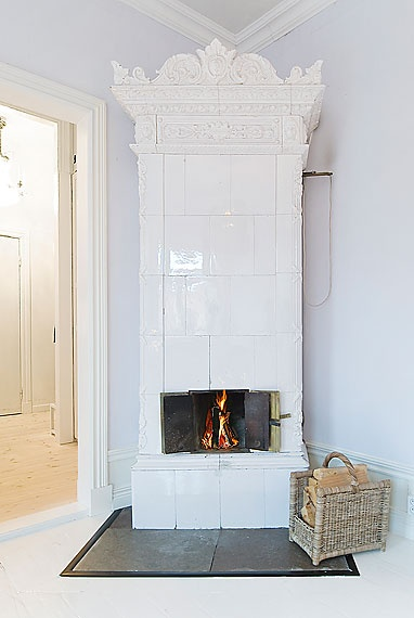 """These types of fireplaces, called """"kakelugn"""" in Swedish, are very common in old Swedish apartments, but they are usually quite understated with white tile and small metal doors that open so you can see the fire."""