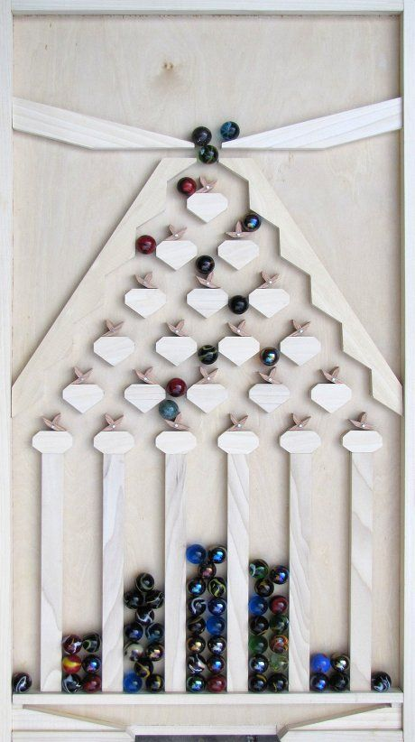 Wooden marble run produces a normal distribution of marbles.