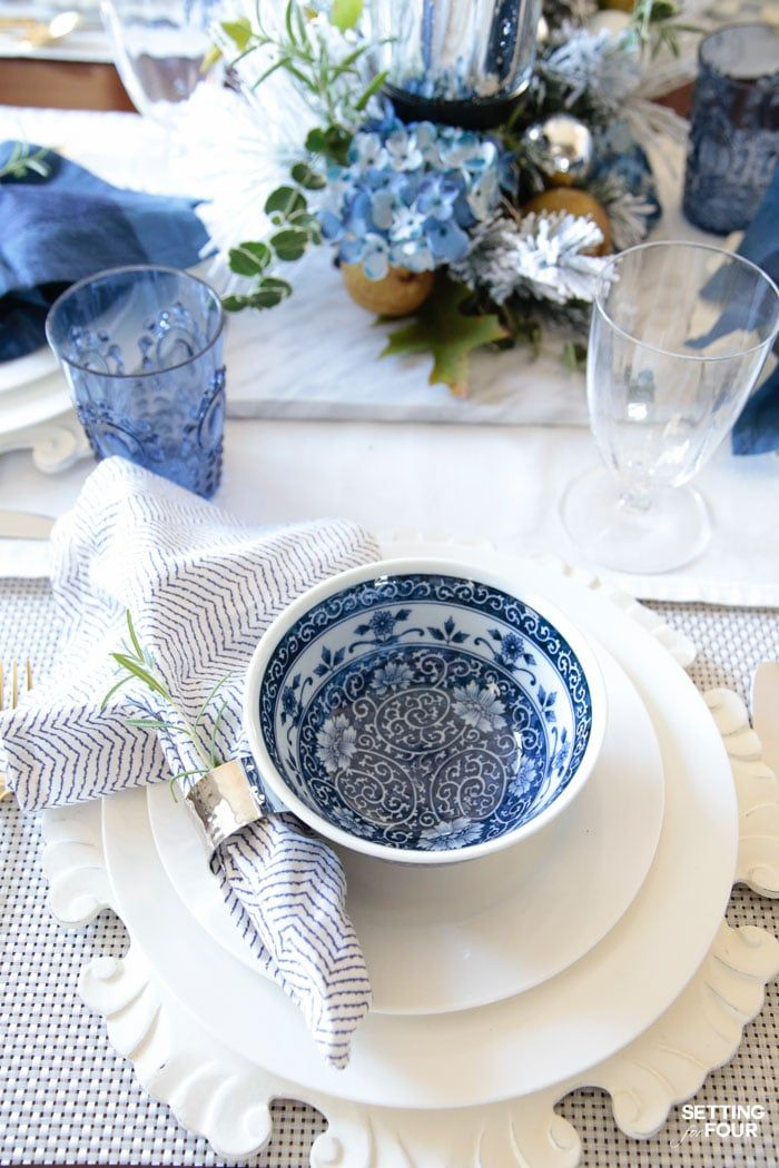 Learn how to create these elegant fall table settings with a blue and white color palette using white dishes, blue and white chinoiserie bowls, navy napkins, sparkly mercury glass and a transitional holiday centerpiece accented with fall herbs, garden greenery and orchard pears.