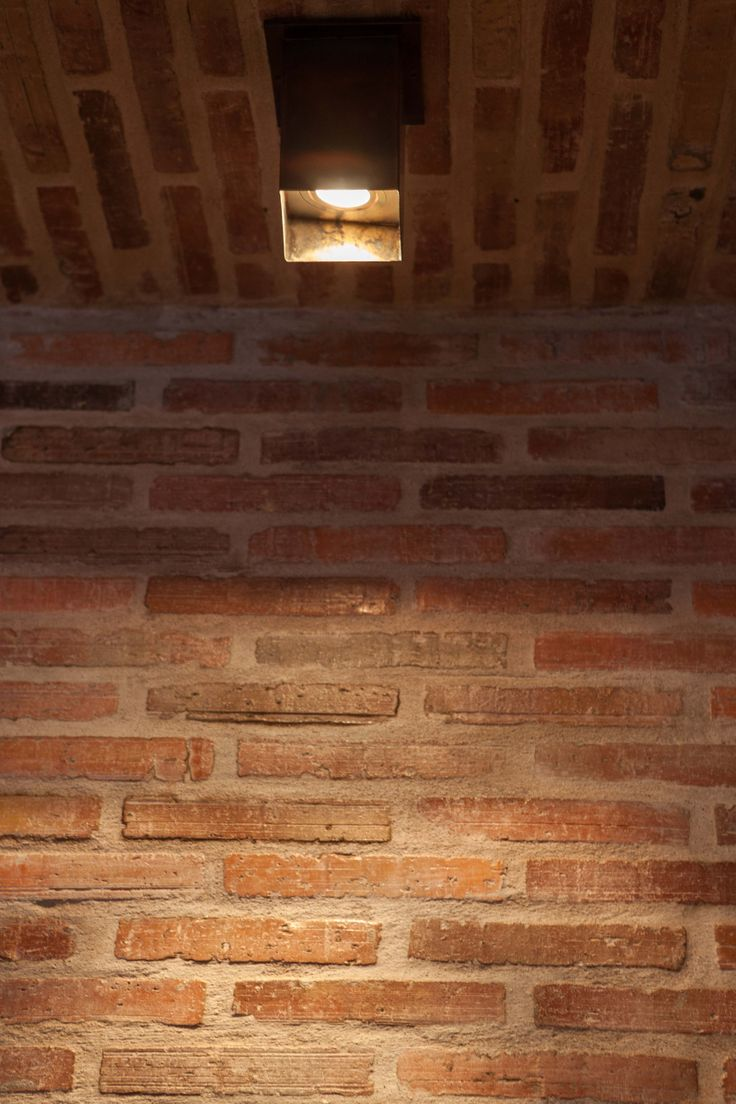 Brass box with recessed low-voltage light with Lanes Ceramic Works klompie bricks cladding the wall