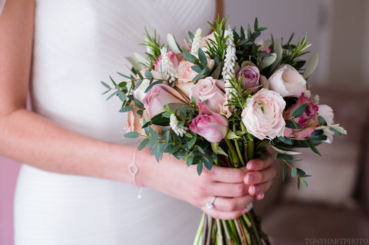 Hand tied Spring Bridal Bouquet of dusky pinks for Farnham Castle Bride created by Eden Blooms Florist.  Made from Hanoi Ranunculus, Rosemary, White Muscari, Memory Lane Rose, Quicksand Rose, Amnesia Rose, Menthe Rose, Olive, Eucalyptus Parvifolia.  Image by Tony Hart www.tonyhartphoto.co.uk