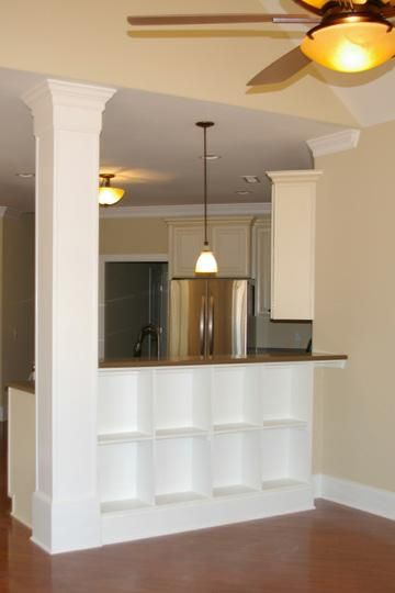 Kitchen leading to the dining area with a built in breakfast nook and a bookcase/cutlery shelf