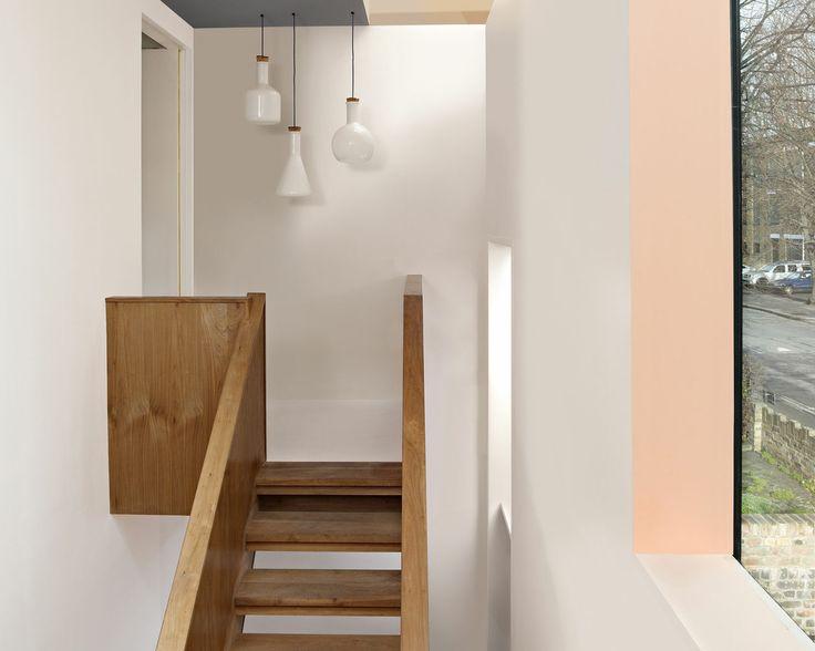 N'oubliez pas le cinquième mur : le plafond. Le plafond gris foncé agrandit le volume de ce couloir étroit et haut sous plafond. Il fait office de guide vers l'escalier en bois.