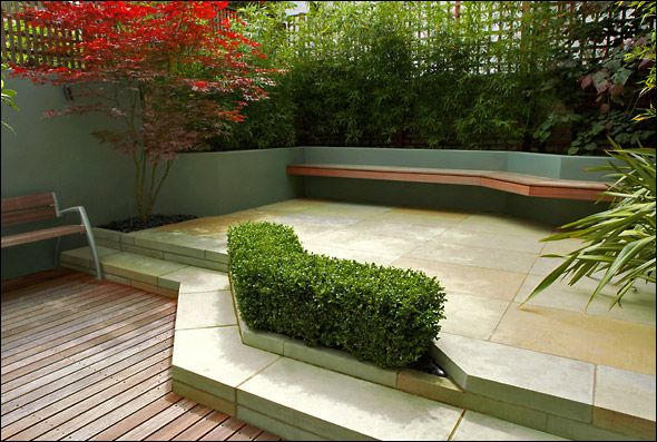The low Box hedge creates a lower patio and an upper sandstone garden which is defined by a cantilevered bench for dining. The lower deck features another smaller bench for a private moment. Bamboo is planted at the base of the raised beds allowing lighting to project upwards