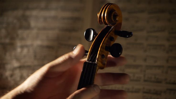 Violinist's hands tuning a violin before the perfomance. Close up shot with dramatic concert lighting and musical notes on background. 4K, UHD  #shutterstock #shutterstockfootage #musician #musicfootage #shutterstockmusic #violinfootage #violinmaster #musicbackground #videobackground #footagebackground #buyfootage #footageonline