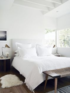 all white bedding with bench