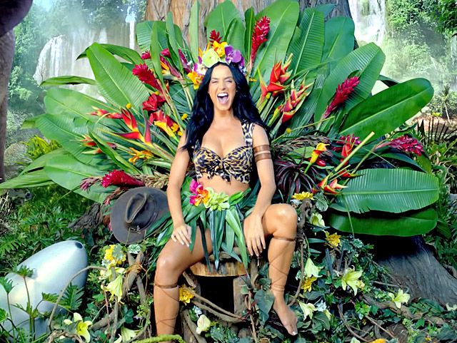 "Queen of the Jungle! Katy Perry fearlessly adjusts to island life while still looking fashionable in a cleavage-baring, animal-print bra top and grass skirt in her music video. ""Roar"" is the lead single from Perry's fourth studio album, Prism."