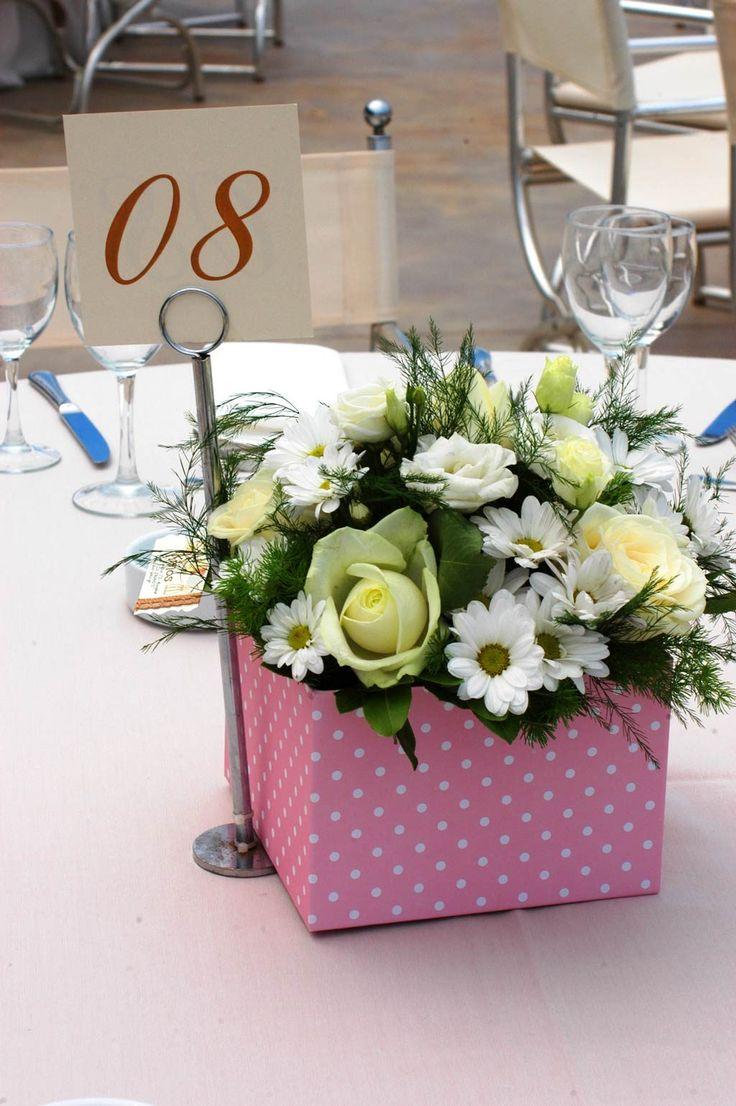 Για την κεντρική διακόσμηση των τραπεζιών χρησιμοποιήθηκαν όμορφα κουτιά γεμάτα με φρέσκα λουλούδια. Ροζ και λευκό σε πουά σχέδιο ήταν τα κουτιά στα μισά τραπέζια για το γλυκό μας κοριτσάκι, τη Μυρτώ
