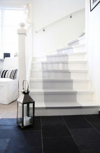 Escaliers en bois repeints avec deux couleurs de peinture gris et blanc qui s'harmonisent avec la couleur des murs et celle du carrelage noir de l'entrée