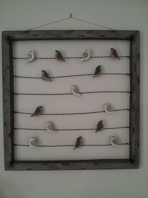 Birds on a wire within a wooden frame