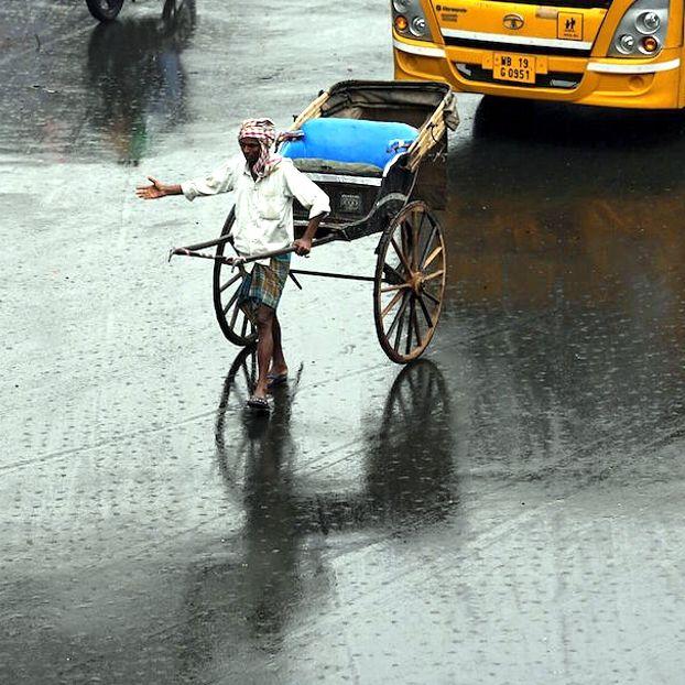 Un uomo tira un risciò sotto la pioggia #Calcutta #India