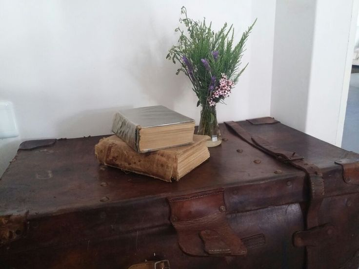 Old books, an old suitcase and a simple bunch of flowers. kimisselfcateringguestcottage.com