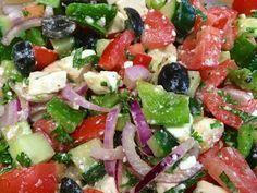 Griekse salade - 200 gr griekse feta. 4 tomaten. 1/2 komkommer. 100 gr pitloze zwarte olijven. 1 rode ui. 1 groene paprika. 1/2 thl gedr oregano. 2 takjes verse munt. 1 takje verse peterselie. 2 el rode wijnazijn. 3 el extra-virgine olijfolie. peper en zout. -