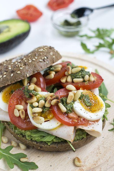 Een goed gevuld broodje gezond met avocado. Een bagel met avocado, kipfilet, tomaat, ei en groene pesto. Een heerlijke combi.