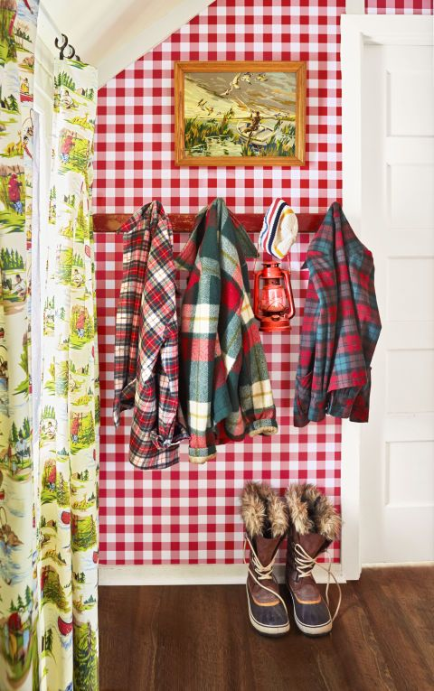 """The entry of the 1930s cottage sets a happy, more-is-more tone with Rudolph-red gingham wallpaper and fishing- themed draperies. """"As corny as it sounds,I feel like this house wraps its arms around you,"""" says homeowner Maria Starzyk. Flannel and wool shirts hang alongside a lantern that's as useful as it is decorative. """"The power goes out here every now and then!"""" says Maria. (Wallpaper, $22 per roll; discountwallcovering.com)"""