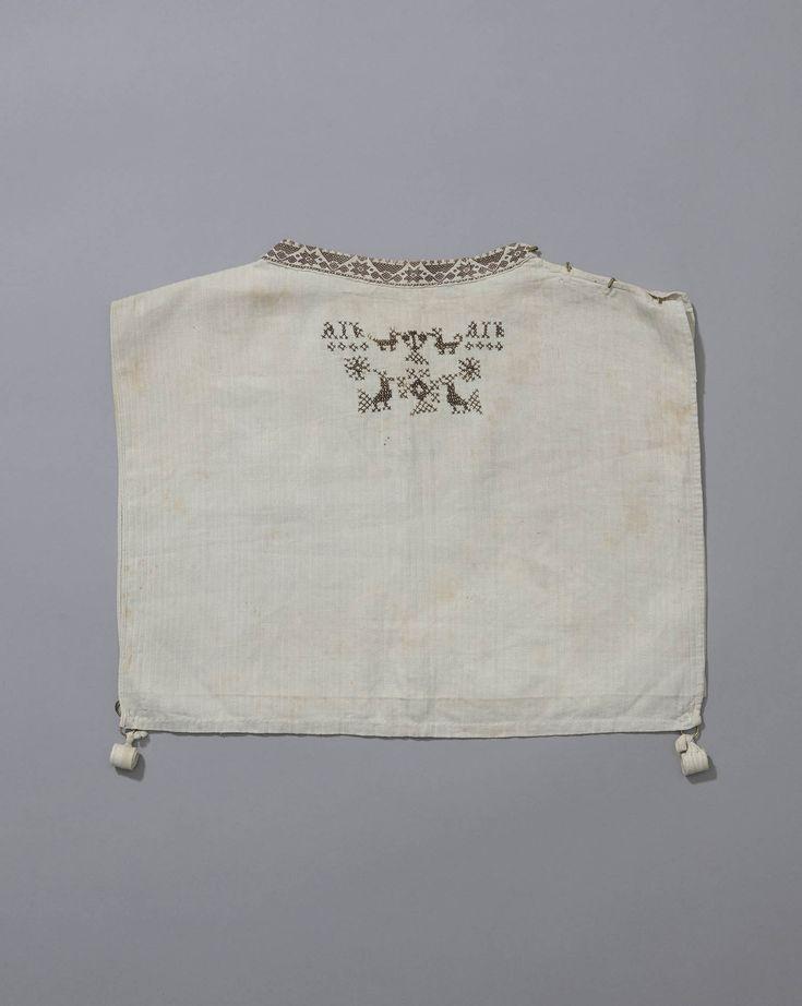 kroplap, Schokland, circa 1870 kroplap van (vermoedelijk) dimet, aan de hals afgezet met langetband en aan de voorzijde versierd met kruissteekmotieven. Het is helaas niet bekend van welke draagster de initialen A I K afkomstig zijn. #Schokland