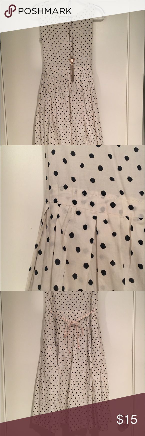 Uniqlo black and white polka dot dress Uniqlo black and white polka dot dress with lined skirt and tie back. Lightweight and perfect with low heels and a necklace. Hits 5'7 woman about mid calf. Uniqlo Dresses