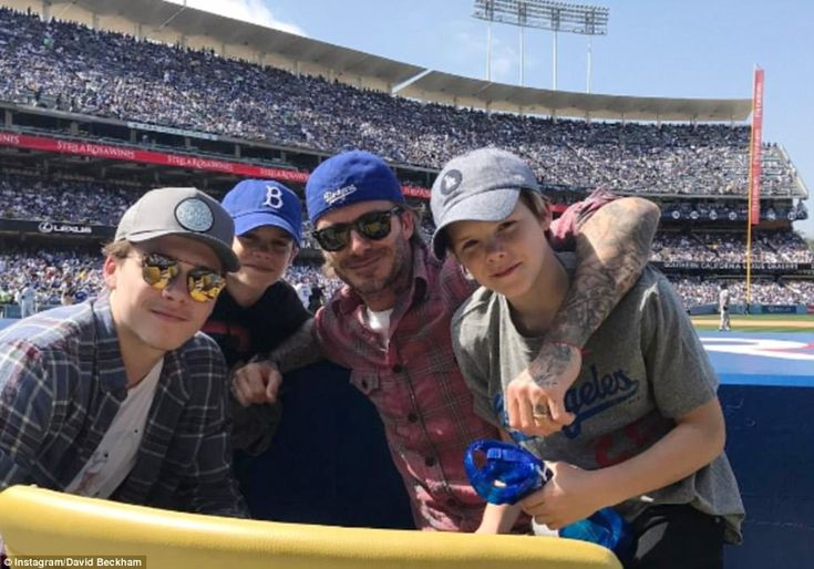 Boys' day out:While Victoria was launching her new collection, David and sons Brooklyn, Romeo and Cruz instead enjoyed a boys' day out at the first Dodgers game of the season as soon as they landed across the pond (above)